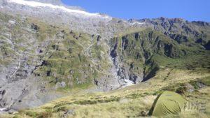 Tent pitched below cliffs